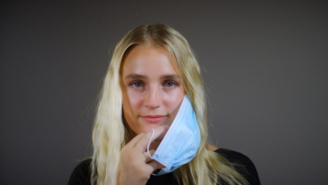 Young-Blonde-Woman-Removes-Face-Mask-Smiles