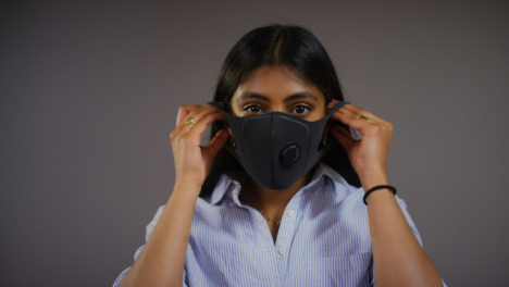 Young-Woman-Puts-On-Face-Mask-Pan-Copy-Space
