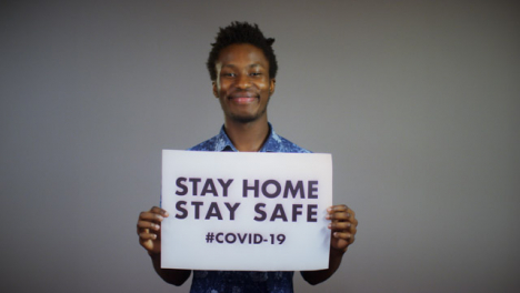 Young-Man-Rips-Stay-Home-Stay-Safe-Sign