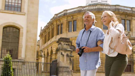 Low-Angle-Shot-of-Middle-Aged-Tourist-Couple-Walk-Around-City