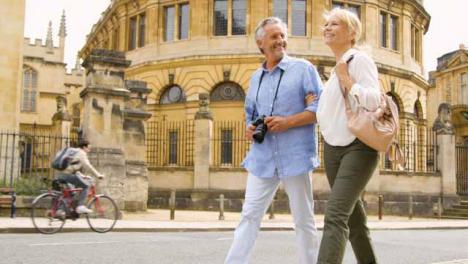 Low-Angle-Shot-Eines-Touristenpaares-Mittleren-Alters-Das-Die-Straßen-Der-Stadt-Erforscht