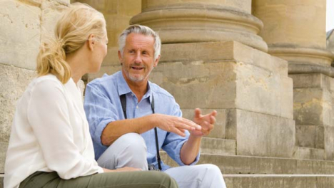 Medium-Shot-of-Middle-Aged-Couple-Sitting-On-Steps-Laughing