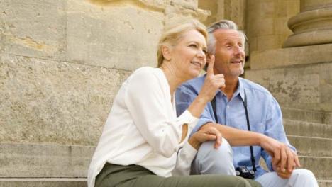 Medium-Shot-of-Middle-Aged-Tourist-Couple-On-Steps-Talking