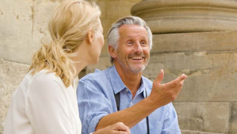 Close-Up-of-Middle-Aged-Tourist-Couple-Laughing-On-Steps-