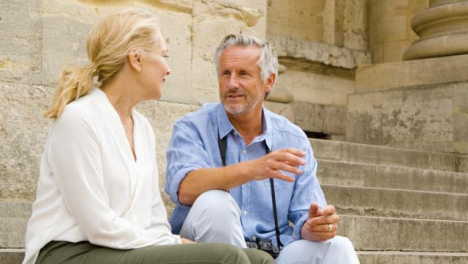 Medium-Shot-of-Middle-Aged-Tourist-Couple-On-Old-Steps-Laughing