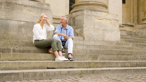 Low-Angle-Shot-of-Laughing-Middle-Aged-Tourist-Couple-On-Old-Steps