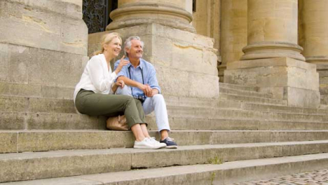 Low-Angle-Shot-of-Middle-Aged-Tourist-Couple-Sitting-On-Old-Steps