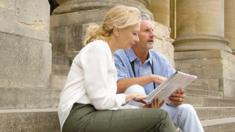 Medium-Shot-of-Middle-Aged-Tourist-Couple-Reading-Map-On-Steps