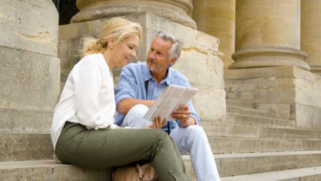 Wide-Angle-Shot-of-Middle-Aged-Tourist-Couple-Reading-Map-On-Old-Steps-