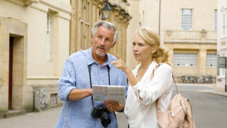 Tracking-Shot-of-Middle-Aged-Tourist-Couple-Reading-Map