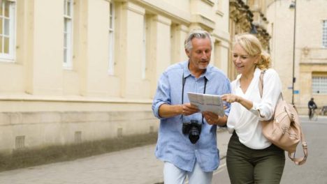 Tracking-Shot-of-Middle-Aged-Tourist-Couple-Reading-Map-Together