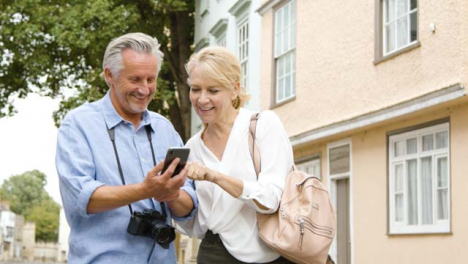 Low-Angle-Shot-of-Middle-Aged-Couple-Reading-Map-On-Phone