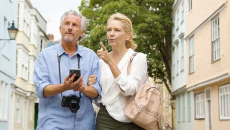 Medium-Shot-of-Middle-Aged-Couple-Reading-Map-On-Phone