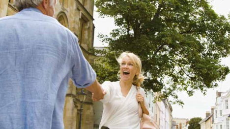 Low-Angle-Tracking-Shot-of-Playful-Middle-Aged-Woman-Leading-Husband-