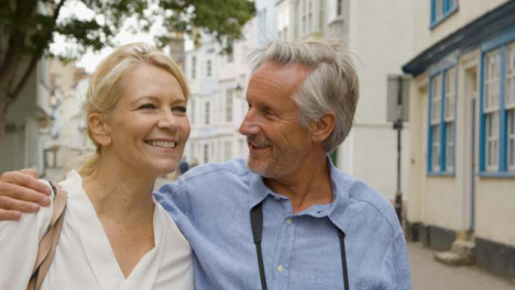 Tracking-Close-Up-of-Middle-Aged-Tourist-Couple-Reviewing-Their-Photos-
