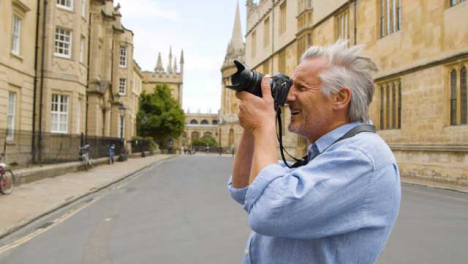 Tracking-Close-Up-of-Middle-Aged-Tourist-Taking-Photo-In-City