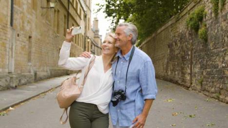 Medium-Tracking-Shot-of-Middle-Aged-Tourist-Couple-Taking-Selfie-