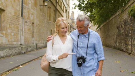 Medium-Tracking-Shot-of-Middle-Aged-Tourist-Couple-Taking-a-Selfie-