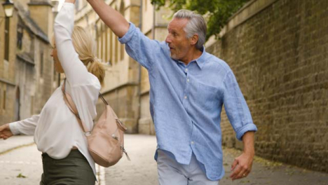 Medium-Tracking-Shot-of-Joyful-Middle-Aged-Couple-Exploring-City
