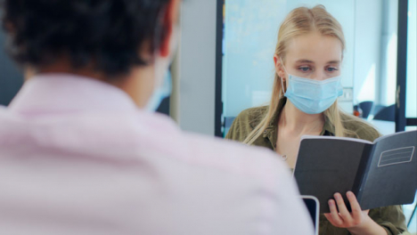 Over-the-Shoulder-Pan-of-3-Colleagues-In-Face-Masks-Working