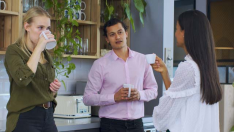 Medium-Tilt-Shot-of-Colleagues-Talking-During-Tea-Break