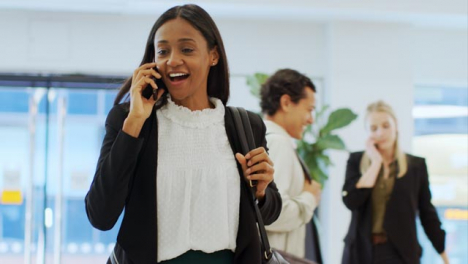 Tracking-Shot-of-Woman-On-Phone-Walking-Through-Office-Building-Lobby