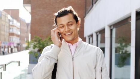 Tiro-De-Seguimiento-Del-Hombre-En-El-Teléfono-Caminando-Fuera-Del-Edificio-De-Oficinas