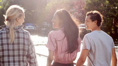 Tracking-Shot-of-3-Friends-Enjoying-a-Walk-Next-to-Canal