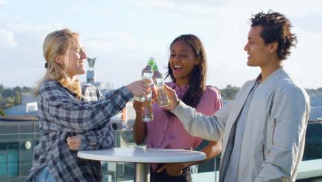 Medium-Shot-of-3-Friends-Enjoying-a-Rooftop-Drink