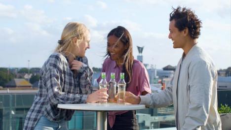 Medium-Shot-of-3-Friends-Enjoying-a-Drink-On-City-Rooftop
