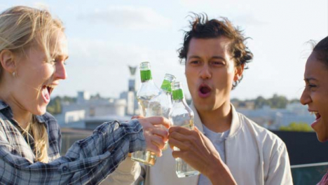Close-Up-of-3-Friends-Enjoying-a-Drink-On-City-Rooftop