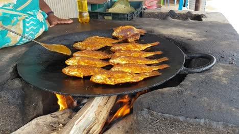Pescados-Picantes-Que-Se-Fr�en-En-Una-Gran-Sart�n-De-Hierro-Fundido-En-Un-Restaurante-Al-Lado-De-La-Carretera-Hogenakkal-Tamil-Nadu-India-Pescados-Picantes-Se-Fríen-En-Una-Gran-Sartén-De-Hierro-Fundido-En-Un-Restaurante-Al-Lado-De-La-Carretera-Hogenakkal-Tamil-Nadu-India