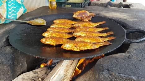 Pescados-Picantes-Que-Se-Fr�en-En-Una-Gran-Sart�n-De-Hierro-Fundido-En-El-Restaurante-Al-Lado-De-La-Carretera-Hogenakkal-De-Tamil-Nadu-India-Spicy-fishes-being-fried-in-big-cast-iron-pan-in-road-side-eatery-Hogenakkal-Tamil-Nadu-India