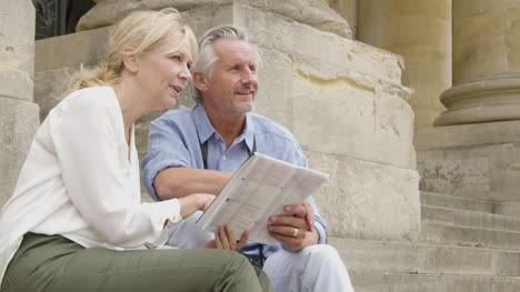 Medium-Shot-of-Middle-Aged-Tourist-Couple-Reading-Map-On-Old-Steps