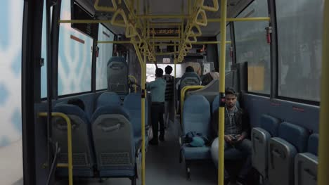 Wide-angle-shot-of-the-inside-of-a-public-bus-during-day-time-less-crowded-due-to-corona-virus-fear