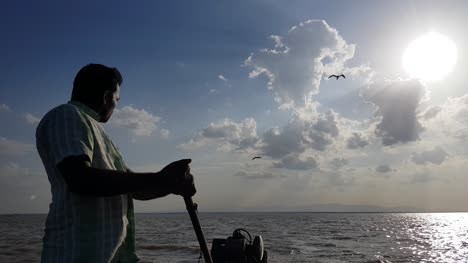 Irukkam-Island-Andhra-Pradesh-India-July-22-2019-Wide-angle-view-of-a-boat-man-driving-a-motorboat-with-dramatic-sky-and-clouds-in-the-background