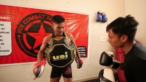 Two-adult-men-training-in-boxing-with-gloves-and-chest-pads-inside-a-room-during-daytime