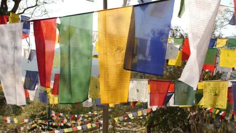 Schöne-Aufnahme-Von-Bunten-Buddhistischen-Flaggen-Die-An-Einem-Sonnigen-Tag-Auf-Einem-Seil-Im-Wind-Flattern-