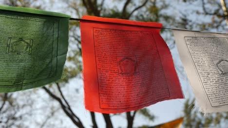 Schöne-Aufnahme-Von-Bunten-Buddhistischen-Flaggen-Die-An-Einem-Sonnigen-Tag-Am-Seil-Im-Wind-Flattern-