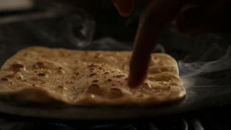 Slow-motion-close-up-of-steaming-hot-roti-cooked-on-a-cast-iron-pan-and-flipping-with-bare-hands