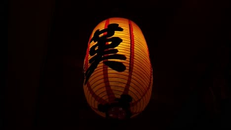 Closeup-of-an-illuminated-Chinese-lantern-lamp-with-the-letter-KA-written-in-Chinese-shaking-in-the-wind