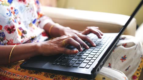 Closeup-of-the-hands-of-a-woman-wearing-golden-bangles-and-ring-using-a-laptop