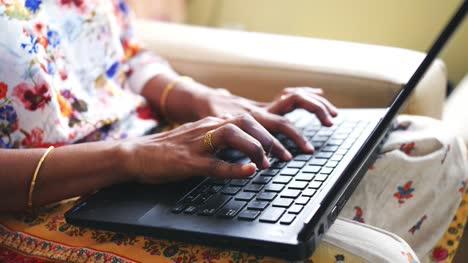 Primer-Plano-De-Las-Manos-De-Una-Mujer-Que-Llevaba-Brazaletes-De-Oro-Y-Anillo-Usando-Una-Computadora-Portátil
