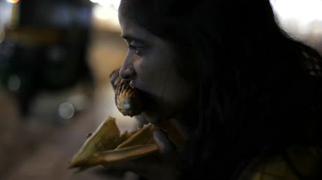 Close-up-of-an-Asian-south-Indian-woman-eating-corn-from-a-cob-during-evening-with-the-traffic-in-the-background-