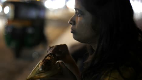 Close-up-of-an-Asian-south-Indian-woman-eating-corn-from-a-cob-during-evening-with-the-traffic-in-background-
