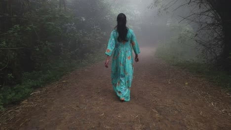 Wide-angle-shot-of-a-woman-wearing-a-dress-walking-through-thick-fog-in-a-forest-during-early-morning