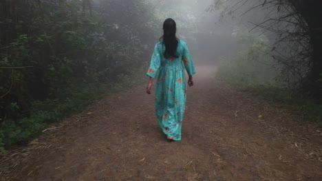 Disparo-De-Gran-Angular-De-Una-Mujer-Con-Un-Vestido-Caminando-A-Través-De-Una-Espesa-Niebla-En-Un-Bosque-Durante-La-Madrugada-Wide-angle-shot-of-a-woman-wearing-a-dress-walking-through-thick-fog-in-a-forest-during-early-morning