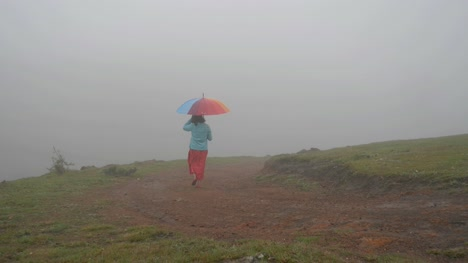 Wide-angle-shot-of-a-South-Indian-woman-walking-with-a-colorful-umbrella-on-a-hill-top-during-a-foggy-morning