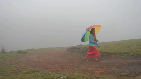 Wide-angle-of-South-Indian-woman-walking-with-a-colorful-umbrella-on-a-hill-top-during-a-foggy-morning