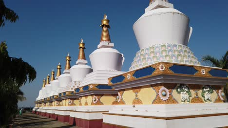 Kollegal-Karnataka-India-March-14-2020-Wide-angle-tilt-down-jib-shot-of-Buddhist-prayer-Stupas-at-the-Dhondenling-monastery-on-a-bright-sunny-day
